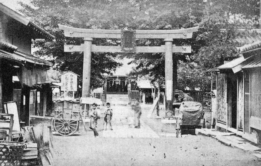 古写真:湯島天神銅鳥居。通りの道がずいぶんと狭い。現在の道はだいぶ拡張されています。