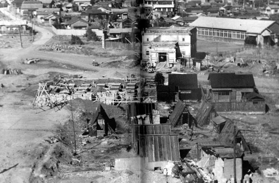 古写真:昭和22年の播磨坂下あたり。中央上の白い建物、焼け残った宗慶寺の納骨堂と、手前にはバラックが写っています。