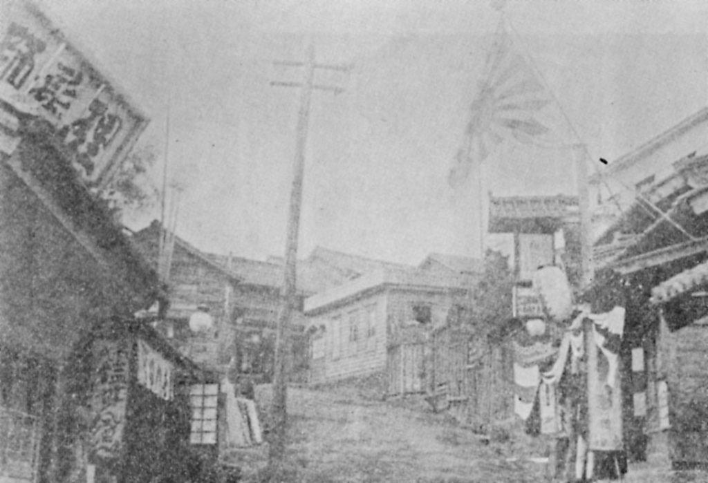 明治後期、神楽坂の藁店。左側に理髪師の看板。右は寄席。