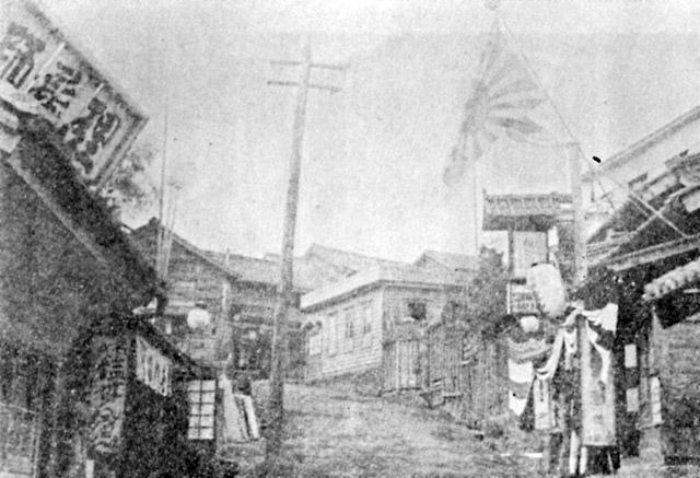 明治後期、神楽坂の藁店。左側に「理髪師」の看板。右側は寄席。